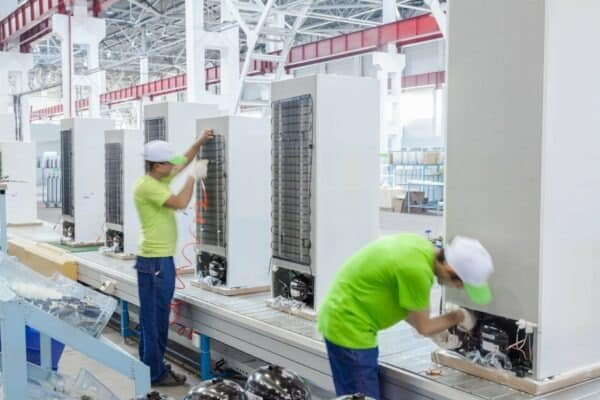 factory floor for production and assembly of household refrigerators on the conveyor belt. factory workers collect refrigerators on the conveyor belt